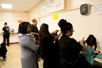 Cosmetology students practicing in class