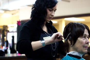 Student giving client a hair trim